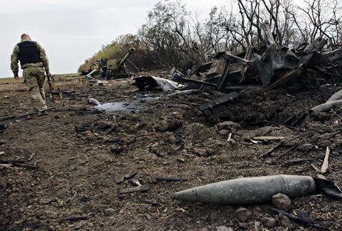 A Ukrainian service member walks past destroyed military equipment near the village of Talakovka, northeast of Mariupol, on Sept. 7 after an overnight bombing.