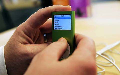A consumer examines a just-released iPod nano at the Apple Store on Fifth Avenue in New York. The update on the popular music player sports a thinner design, five colors, a new search function and longer battery life.