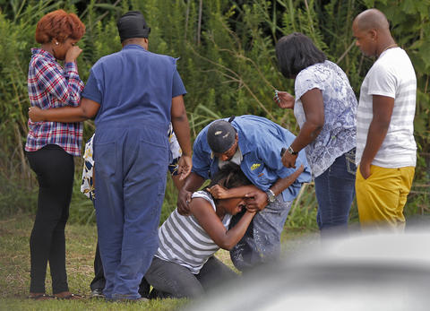 Staff Photo Of The Week: Aug 9-Aug 15, 2014 Family members grieve at the scene of where two Newport News' men drowned while swimming in Deep Creek Tuesday afternoon.
