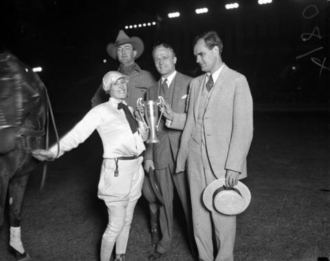 Tad Lucas, from left, Tex Austin, manager of the rodeo, Robert E. Corcoran, Vice President of the Association of Commerce, and Robert B. Witner, chairman of General Civic Affairs, award Lucas with a trophy for winning the cowgirl portion of Chicago's World Championship Rodeo held at Soldier Field in August of 1927.