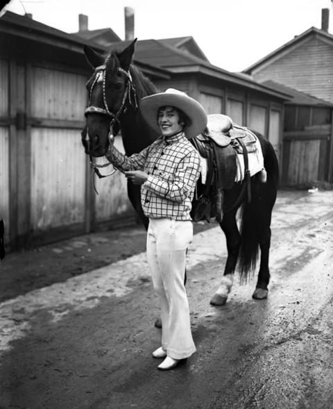 "Famous cowgirl Tad Lucas, of Forth Worth, Texas, with her horse in Chicago, circa Nov 1929. Lucas, also known as ""Rodeo's First Lady,"" was in town to compete in a rodeo at the Chicago Stadium in November of 1929. She won the cowgirls' trick riding championship at the event and was awarded the H. Gordon Selfridge trophy as the champion all-around cowgirl."