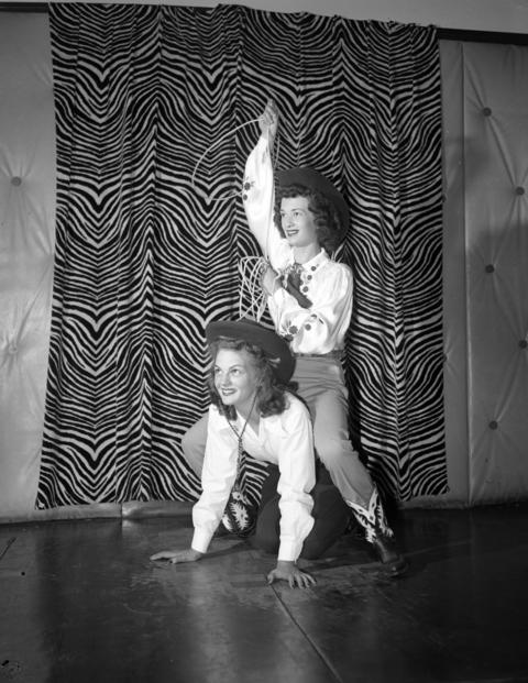 Model Toni Berry swings a rope as she rides model Betty Frost at the Rodeo Queen eliminations at Patricia Stevens Model Studio on July 12, 1947. The contest was for the Chicago Championship Rodeo that year.