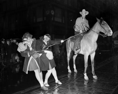 Champion roper Wiley Elliott ropes Virginia Hanke and Anne Marie Weirup during a rodeo, circa March 1944.