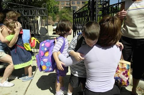 Lisa Rynearson (left) hugs daughter Mia, 5, as Karen Mondry greets her twins, Sari and Elliott, 5, at Ogden Elementary in Chicago. The children were scheduled to leave at noon, but many parents took their children out of schools and businesses early with news of the terrorist attacks.
