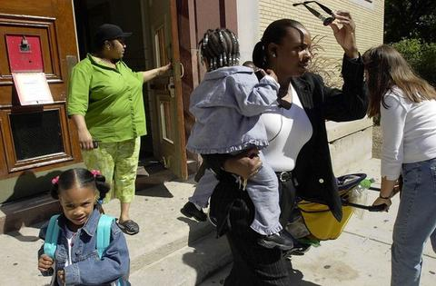 Anette Johnson (left) holds the door for her son Anthony, 7, as Janice Sandifer leaves Chicago's Ogden Elementary School with her grandchildren,Tia Thompson, 6, and her sister, Nia, 2. Many relatives arrived early at the Gold Coast school to pick up pupils after news of the terrorist attacks on the United States