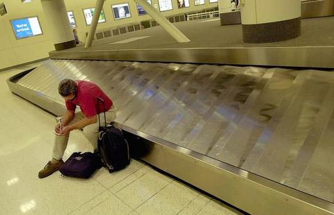 Mike Chasteen of Louisville, Ky., tries his cell phone as he sits on an empty luggage conveyor at Midway Airport in Chicago. Chasteen was trying to get to Dallas, but Midway was shut down due to terrorist attack on the East Coast.