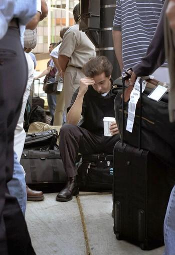 John Nicely (center) sits on his luggage Tuesday as he and other travelers wait at a Hertz rental car office on State Street. Nicely was stranded in the city after his flight to Atlanta was canceled.