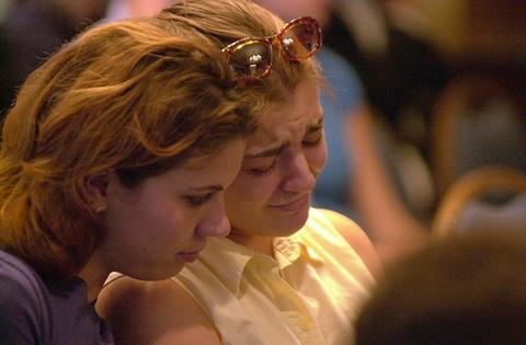 Beck Beattie, left, and and Cindy Hartigan, both students at North Central College in Naperville, Ill., comfort each other during a moment of silent player during aservice at the college on Tuesday. Hartigan stood up during the service and asked for prayers for her boyfriend and friends who live blocks away from the attack in New York. This was the first of two memorial services at North Central College for the victims of the East Coast terrorist attack.