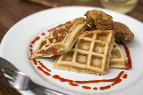 Fried Chicken and Waffles served with hot sauce and syrup at Whisk Chicago, 2018 W. Chicago Ave. in Ukrainian Village.