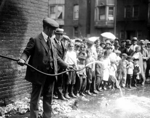 A Prohibition raid in 1923 Chicago shows a man emptying mash used to make whiskey, via a hose, out onto the street in front of a group of children.