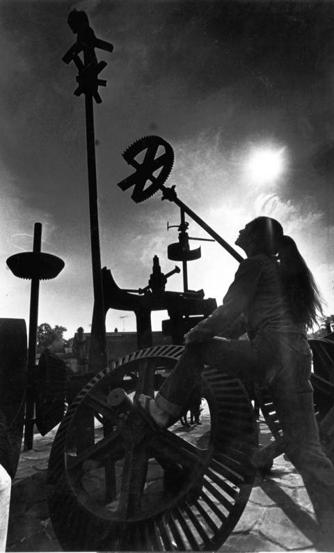 Oct. 28, 1983: Beth Rexford admires old Farm Implement Sculpture in Bennett Mill Park along the Fox River in Geneva.