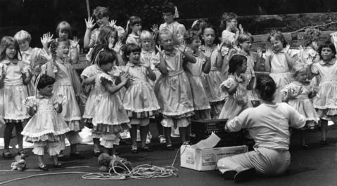 July 30, 1986: Members of the Sunshine Generation perform at Batavia's Windmill City Festival. Leslie Hartsock (left) directs the small vocalists in a hand-waving rendition of a song.