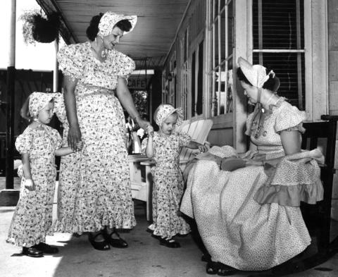 "July 29, 1955: Dressed in ""swish"" costumes, Barabara Harwood, 5, and Linda, 3, with their mother, Mrs. Clarence Harwood, stop to chat with Mrs. Charles Heide."