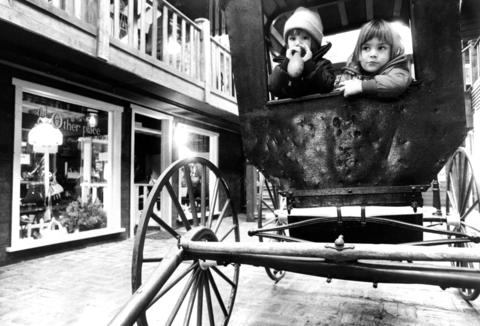 Feb. 6, 1974: Children enjoy the antiquated feel of a carriage in the Grainery shopping center.