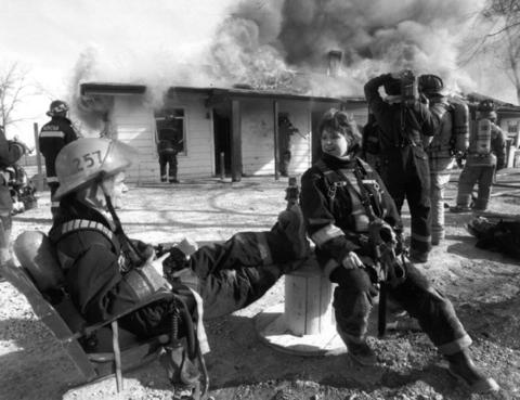 Feb. 1, 1993: Charlotte Clark (left) and Terry Landrey, registered nurses with the Silver Cross Hospital emergency unit in Joliet, relax while a vacant hotel is burned during a fire-fighting class.