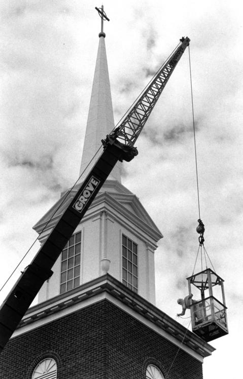 July 12, 1990: Elmer Anderson weathers the heights as he gives St. Anthony's Catholic Church a paint job while swinging from a 75-foot crane.