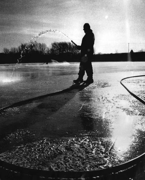 Jan. 13, 1975: Restoring the ice rink's surface after a busy weekend, a Western Springs Park District maintenance worker hoses down the rink on a frigid morning.