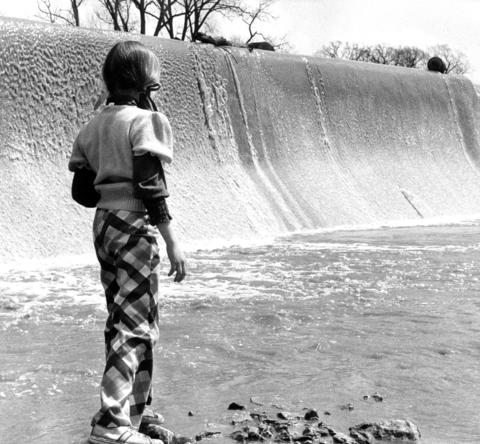April 15, 1974: Amy Korista, 9, listens to the water roar at the bottom of the Hickory Creek dam where people can fish for bullheads.