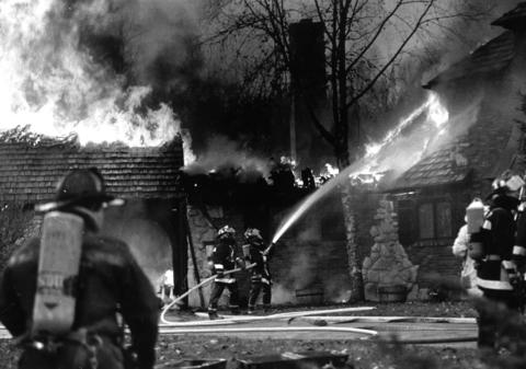 Nov. 17, 1990: Firefighters pour water on a burning house in New Lenox. The fire burned about one-third of a $1.6 million brick house owned by commodity broker James Warning.