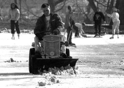 Jan. 21, 1992: Steve Braun, a New Lenox park district worker, uses a bulldozer blade to scrape the ice at a park while children wait for him to finish so they can play hockey.