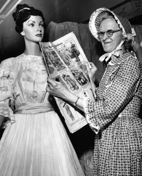 Aug. 18, 1963: Inez Johnson, a hostess at Barrington's centennial headquarters, holds an old copy of the Chicago Tribune. The paper, which was from Sept. 15, 1929, showed fashions popular between 1901 and 1915.