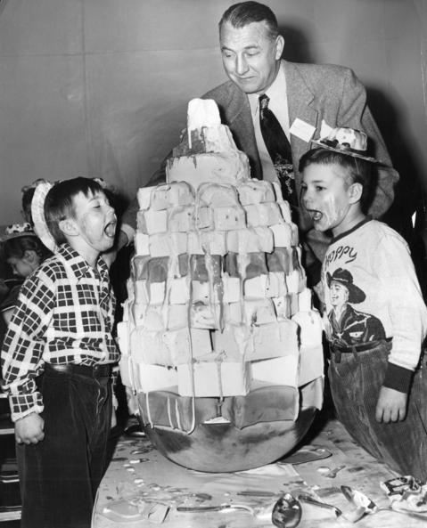 March 19, 1952: Underprivileged boys tackle a tower of ice cream while Hawthorn-Mellody president H.W. Peters eggs them on.