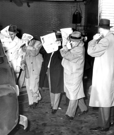 April 19, 1956: Tom Smith (right) of the Internal Revenue Bureau watches as four of eight men seized in a gambling raid are loaded into a patrol wagon for a trip to the Chicago Detective Bureau.