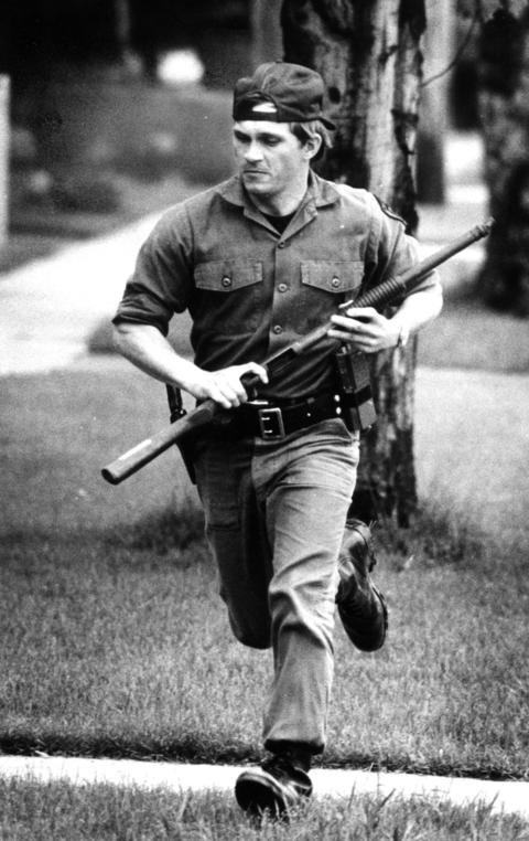 May 27, 1982: A police officer attempts to get close to the house in which James G. Williams barricaded himself. The stand-off lasted more than 19 hours and was the result of Williams chasing his wife out of the house with a gun.
