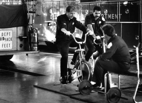 Dec. 11, 1986: Des Plaines paramedic Stephen Foster watches Steve Davis (left) and Tom Heavey work out in their firehouse, where a conditioning program is mandatory for all personnel.