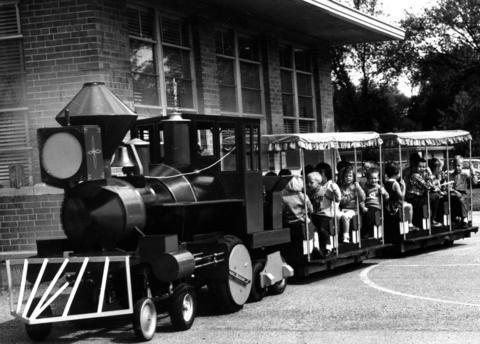 Sept. 26, 1963: Clarendon Hills youngsters make a trial run aboard toy train built for PTA carnival day to be held by Prospect and Walker schools. Paul Rossbach, who designed the vehicle and did most of the construction, served as engineer.