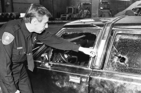 Jan. 23, 1988: Officer Paul Stadwiser inspects damage to the car of Teamster official Dominic Senese, who was critically wounded in a shotgun attack near his Oak Brook home.