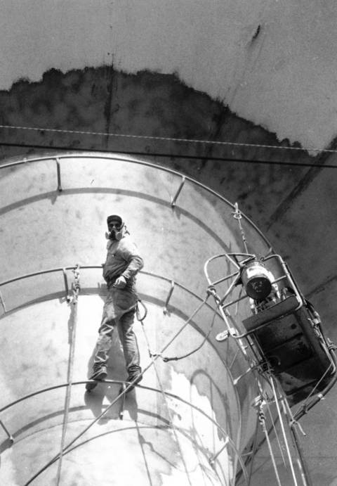 Oct. 19, 1990: James Houck wears a protective mask as he prepares the Oak Brook water tower for a fresh coat of paint.