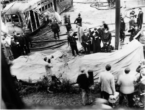 A priest gives last rites to the victims on May 25, 1950 when a Green Hornet street car collided with a fuel truck. It was a grim task to identifying bodies as there wasn't much to go on: burned clothes, melted shoes, a ring, bits of toys, remnants of a letter from a young woman planning her wedding.