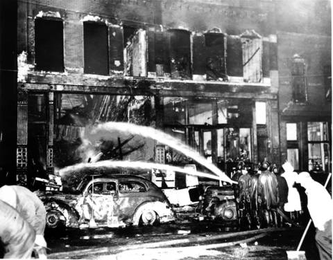 Two parked cars are hosed by firemen after the blaze at 6251 State Street. By most accounts, the streetcar was going too fast for the wet conditions.