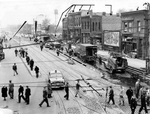 """A general view on May 26, 1950, of the scene north of 63rd and State Streets where a street car and gasoline truck collided the day before, killing 34 people. The streetcar was being switched into a """"turnaround"""" because of flooded conditions of an underpass beneath a viaduct from which this picture was taken. The arrows added show details of the accident, as well as the buildings damaged in the explosion."""