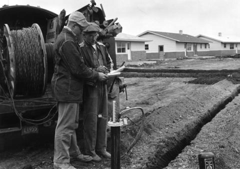 """May 31, 1958: Illinois Bell Telephone company linemen plan for laying buried, """"no-pole"""" cable in Elk Grove Village."""