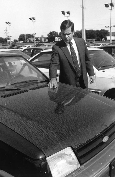 Oct. 4, 1989: David Schmerler checks the damage to new cars at Schmerler Ford in Elk Grove Village after jet fuel was dumped on them.