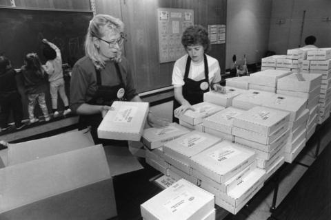 Nov. 24, 1991: Barb Kaltenbach (left) and Elaine Burkot stack food boxes in preparation for Market Day at Clearmont School in Elk Grove Village.