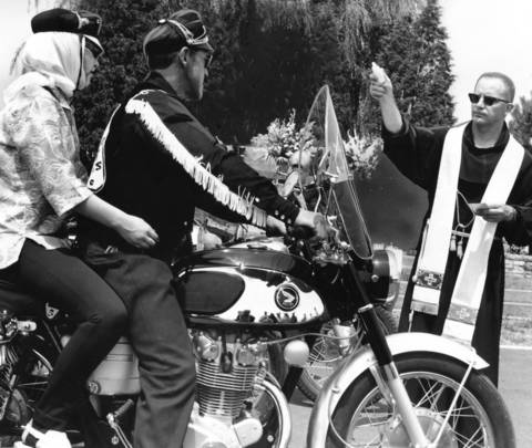 "July 31, 1966: The Rev. Edwin Albers blesses motorcycle riders during the 19th annual St. Christopher Fiesta at St. Christopher Catholic Church in Midlothian. The church holds the ceremony because it is named after St. Christopher, the patron saint of travelers. About 3,000 motorcycle riders attended. It also holds an annual ""blessing of the cars."""