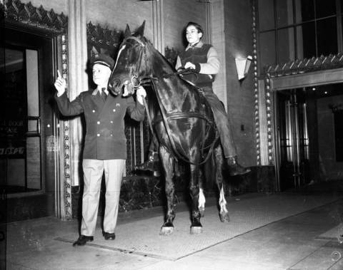 Elevator operator Frank Lofther cues up an elevator for Tom Moore and his horse in the Merchandise Mart on March 10, 1949. The horse was for a television show produced int the building.