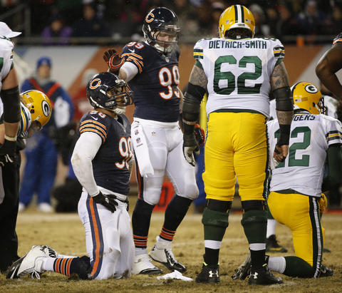 Shea McClellin pats defensive tackle Corey Wootton on the helmet after a pass rush on Packers quarterback Aaron Rodgers, who threw an incomplete pass in the second quarter.
