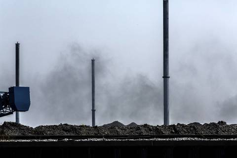 A black dust rises above petroleum coke waste pile as a group of South Side environmental activists takes a boat tour to see giant mounds of petroleum coke piling up along the Calumet River in Chicago on Monday, Sept. 9, 2013.