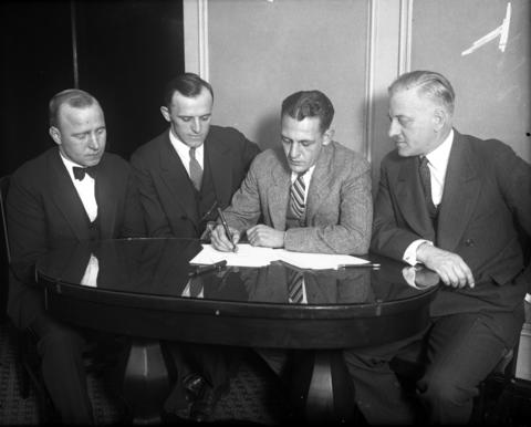 "On Nov. 22, 1925, less than 24 hours after his last game with the Fighting Illini, Harold ""Red"" Grange, second from right, signed a contract to play professional football with the Chicago Bears at the Morrison Hotel in Chicago. Surrounding Grange as he signed are Bears managers Edward C. Sternaman, from left and George C. Halas. Grange's agent, Charles C. Pyle, is on the right."