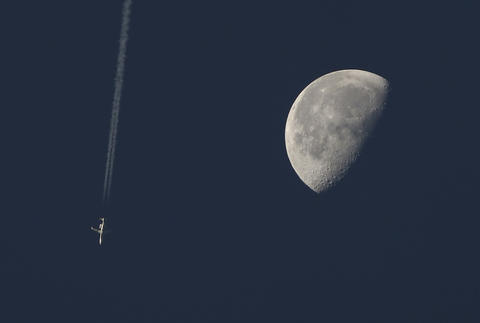 Staff Photo Of The Week: Oct 11-Oct 17, 2014      An early morning flight tracks across the sky with a lunar backdrop early Tuesday morning.
