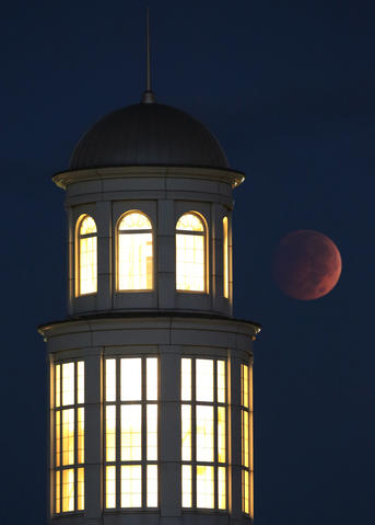 Staff Photo Of The Week: Oct 4-Oct 10, 2014     A full lunar eclipse glows in the early morning sky Wednesday over the Trible Library at Christopher Newport University in Newport News, Va. The eclipse was visible throughout North America, and here in the East between 5:15 a.m., reaching it's reach its peak at 6:25 a.m.