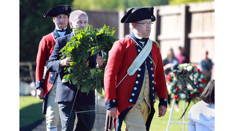 Lance Pedigo, rear, John Harbour, center, Tim Sutphin, front, lay a wreath during the opening ceremonies. Harbour was in the first Williamsburg Fife and Drums in 1958 and the first bass drummer, Talmadge Alphin, was killed in Vietnam in 1968.