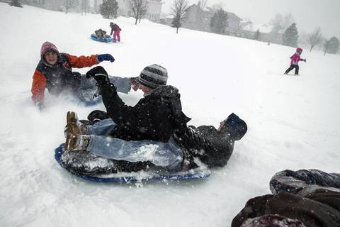 Children enjoy sledding during blizzardlike conditions in Frankfort.