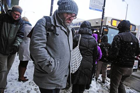 A morning commuter struggles though snow flurries on his way to the CTA Blue Line station earlier this year.