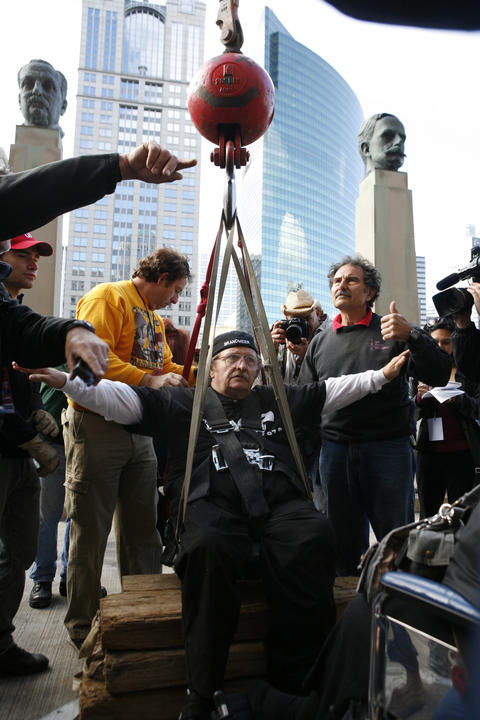 """Mario Wallenda, 64, paralyzed high-wire walker of the famous Flying Wallenda family, is hoisted into his """"Skycycle"""" to make his way across the Chicago River from the Merchandise Mart to Wacker Drive and back again in Chicago."""