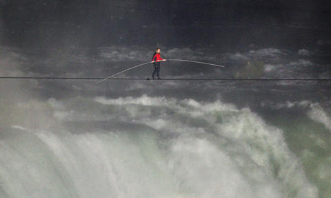Nik Wallenda walks the high wire from the U.S. side to the Canadian side over the Horseshoe Falls in Niagara Falls, Ontario.
